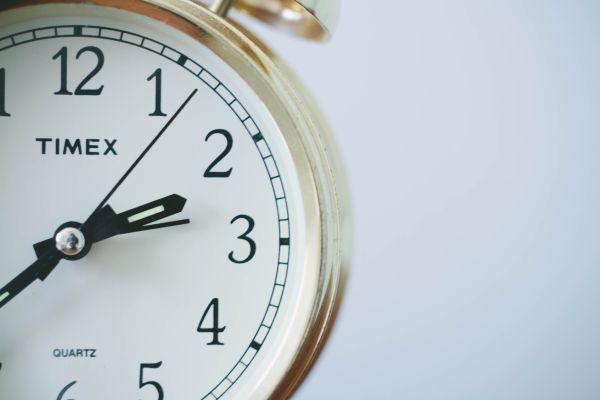 Reloj de agujas de color dorado sobre fondo blanco